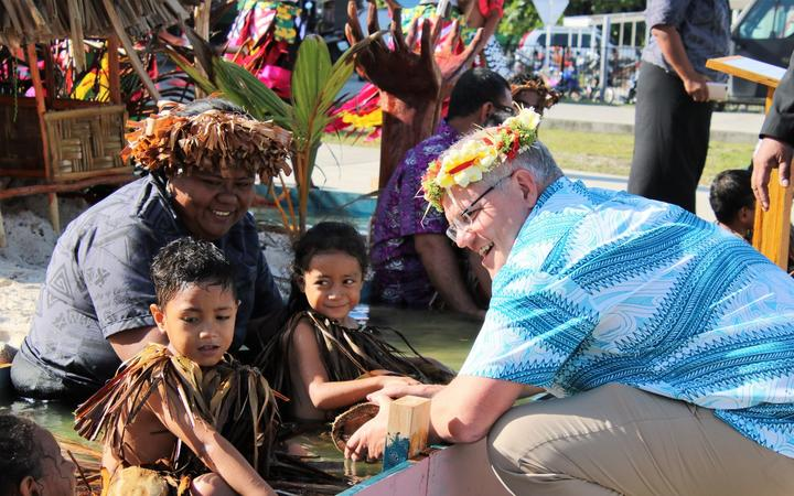 Australian prime minister Scott Morrison speaks to kids at a climate change display in Tuvalu ahead of the Pacific Islands Forum leaders summit on Funafuti. August 2019
