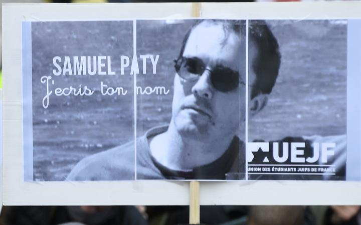 A person holds a placard with the portrait of history teacher Samuel Paty as people gather on Place de la Republique in Paris on October 18, 2020, two days after he was beheaded by an attacker who was shot dead by policemen.
