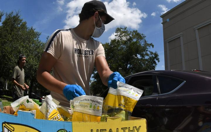 Volunteers distribute food from the Second Harvest Food Bank of Central Florida to the needy at Church in the Son on August 7, 2020 in Orlando, Florida.
