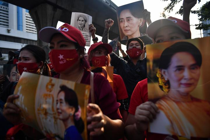 Myanmar migrants hold up portraits of Aung San Suu Kyi as they demonstrae outside the Myanmar embassy in Bangkok on 1 February 2021, over the military coup in Myanmar.