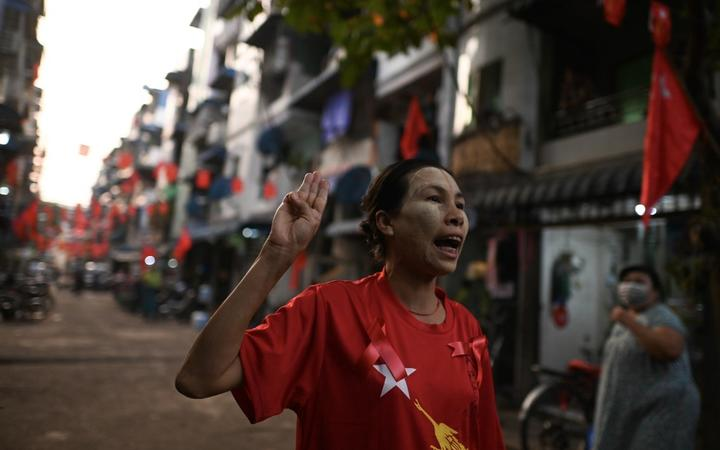 A woman poses for a photo as she holds up the three-finger salute and calls for the release of detained civilian leader Aung San Suu Kyi in Yangon on February 5, 2021,