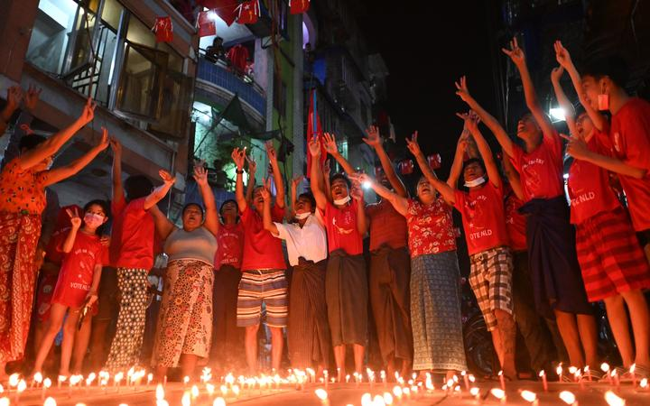 People take part in a noise campaign on the street after calls for protest against the military coup emerged on social media, in Yangon on February 5, 2021.